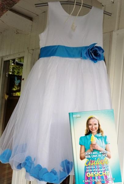 Im Bild halte ich das Buch vor ein weißes Mädchen-Kleid.
