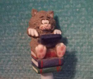 Katze, auf einem Stapel Bücher sitzend und auf einem Laptop tippend