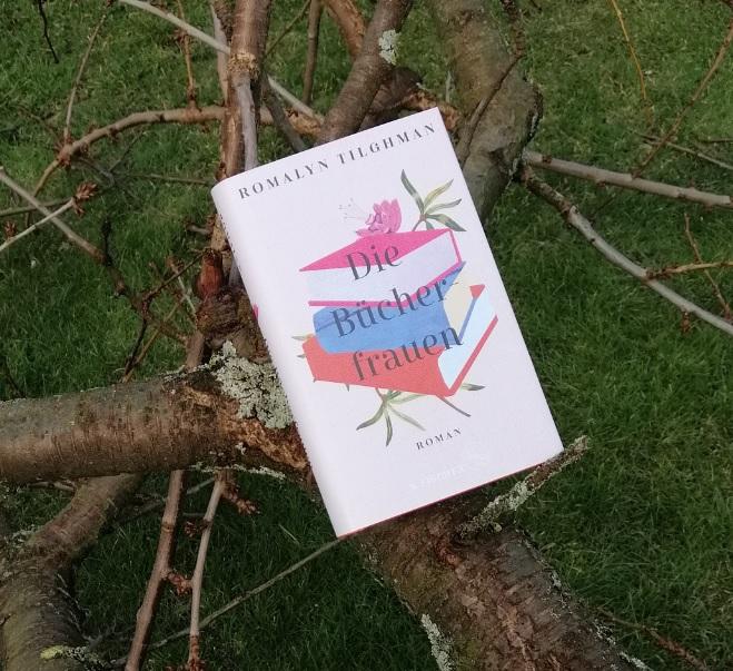Das Buch lehnt in einer Astgabel eines abgesägten Astes, der auf dem Rasen liegt.